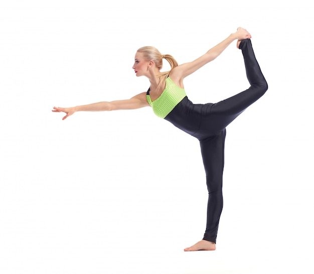 Young woman doing yoga on white balancing on one leg