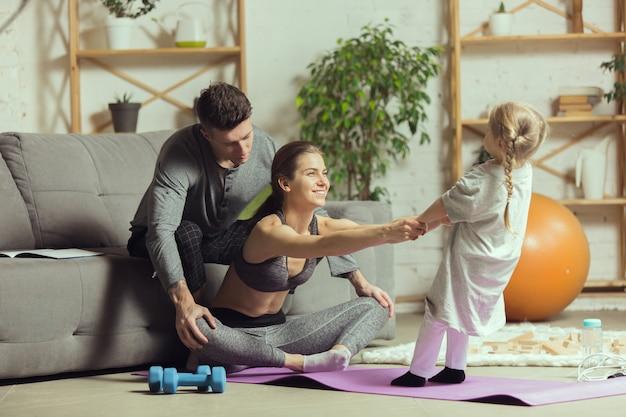 Молодая женщина занимается йогой с дочерью и мужем