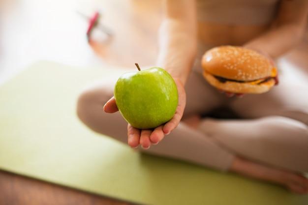 방에 요가 운동을 하 고 젊은 여자. 녹색 건강 한 사과 손에 fatning 햄버거를 들고 여자의보기를 잘라. 어려운 선택입니다. 건강하거나 건강에 해로운 생활 방식.