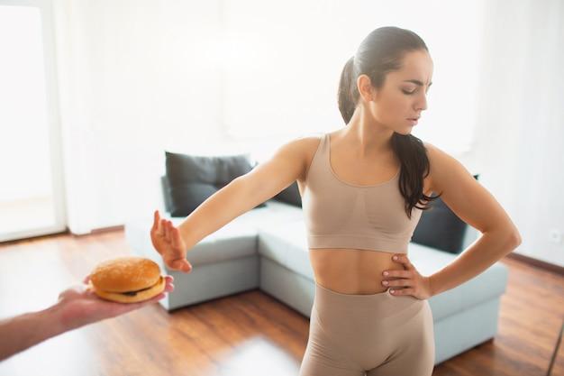 격리하는 동안 방에 요가 운동을 하 고 젊은 여자. 소녀는 햄버거 먹기를 거부합니다.