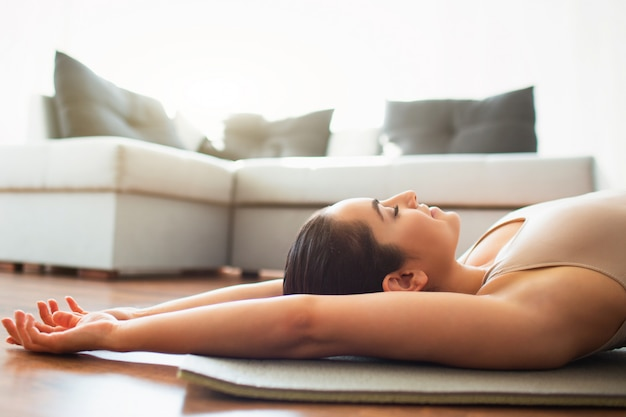 Young woman doing yoga workout in room . cut view of girl lying on mat. rest or relax after exercise. alone in room.