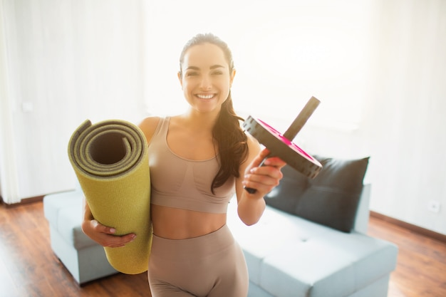 Young woman doing yoga workout in room during quarantine. cheerful positive girl smiling and holding rolled yoga mat and abdominal exercise roller. after training.