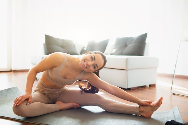 Young woman doing yoga workout in room during quarantine. cheerful positive girl stretching one leg. sit on mat and smile on camera.