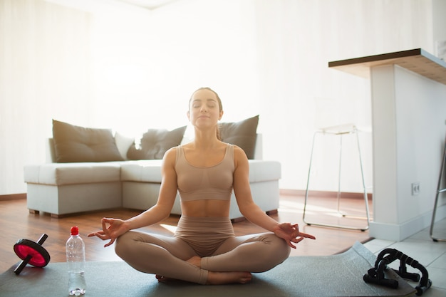 Young woman doing yoga workout in room during quarantine. sit on mat in lotus position with legs crossed. meditating alone in room. water bottle and sports home eqipment besides.