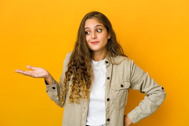 Молодая женщина сомневается и пожимает плечами в вопросительном жесте