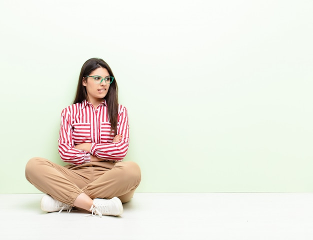 Young woman doubting or thinking, biting lip and feeling insecure and nervous, looking to copy space on the side sitting on the floor