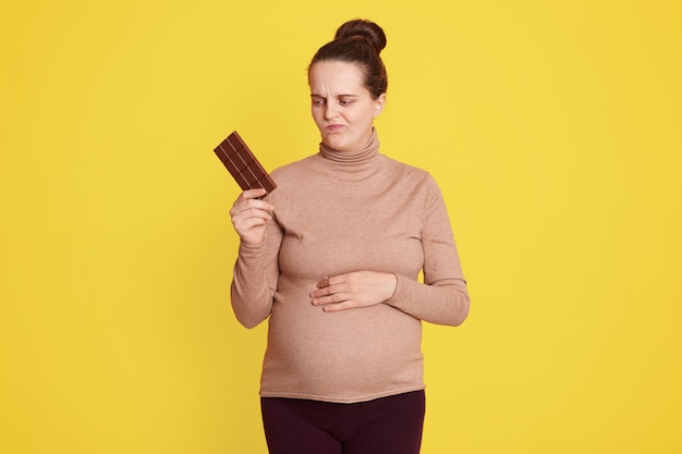 Young woman doubts eating chocolate or not, posing isolated over yellow wall, holding bar of chocolate in one hands and looking with doubting facial expression, need to keep healthy eating.