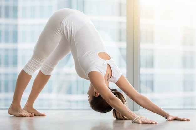 Young woman in downward facing dog pose against floor window