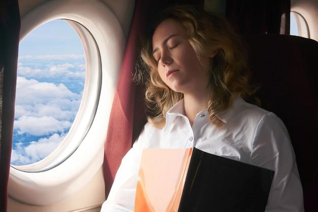 若い女性は、長い飛行中に飛行機のキャビンで居眠りしました
