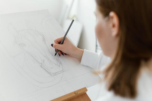 Giovane donna che disegna su una tela