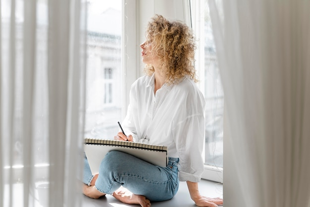 Young woman drawing at home near the window