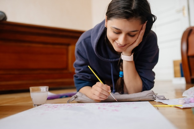 Young woman drawing laying on the floor at home