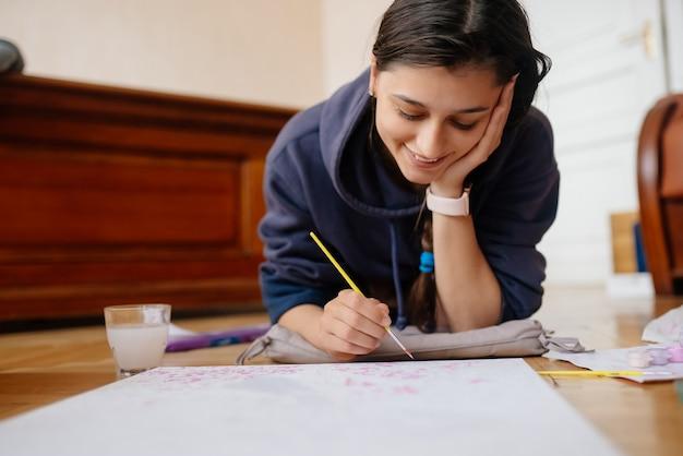 집에서 바닥에 누워 그림을 그리는 젊은 여자