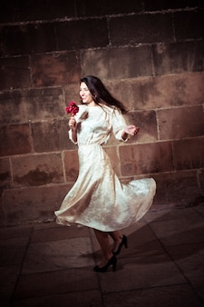 Young woman in dress dancing in street