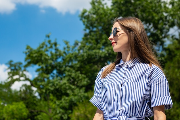 Young woman in dress and glasses stands in the park.