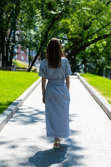 Young woman in dress and glasses walks along the alley in the park.