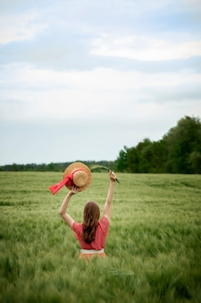 Young woman in dress and hat in green field of barley in countryside. stylish girl in rustic dress enjoying peaceful moment in grass in summer. tranquil rural moment