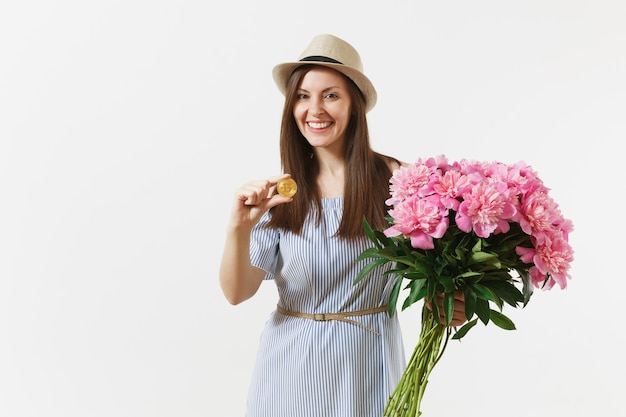 Young woman in dress, hat holding bitcoin, coin of golden color, bouquet of beautiful pink peonies flowers isolated on white background. business, delivery, online shopping, virtual currency concept.