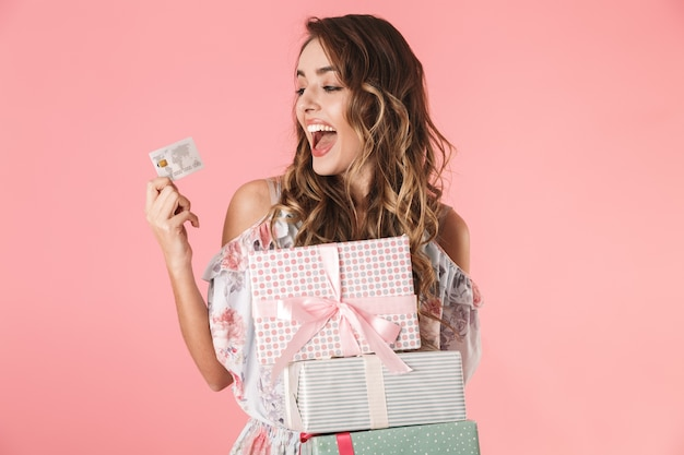 Young woman in dress holding credit card and boxes with purchase, isolated on pink