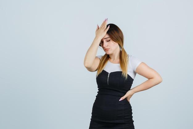 Giovane donna in abito che tiene la mano sulla fronte e sembra esausta