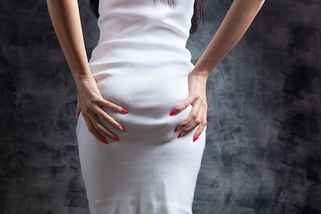 Young woman in a dress holds her butt in her hands