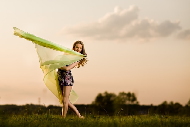 Young woman in dress making gymnastic pose and holding yellow cloth on summer day with field landscape at background