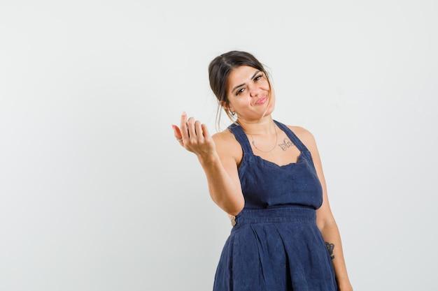Giovane donna in abito in posa mentre è in piedi e sembra deliziosa