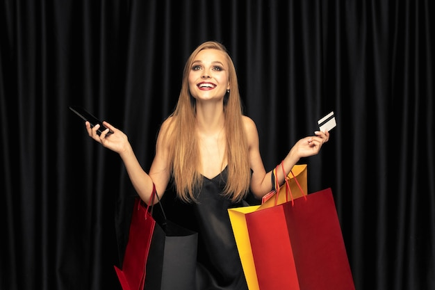 Young woman in dress shopping on black wall