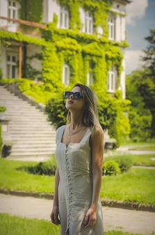 Young woman in dress and sunglasses with old building