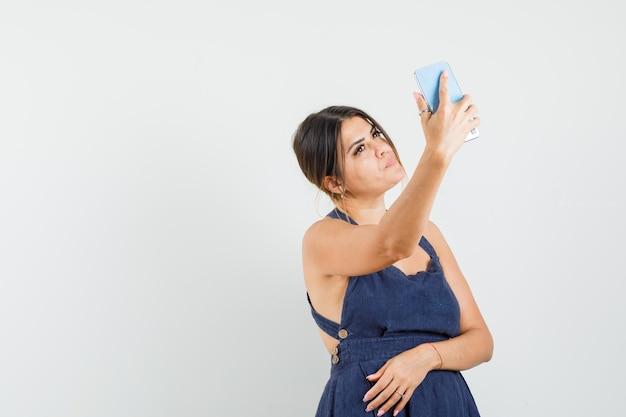 Giovane donna in abito che prende selfie sul cellulare e sembra carina