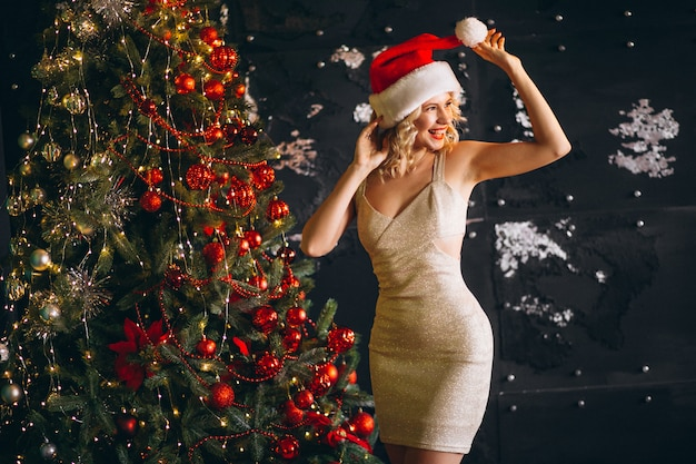 Young woman in dress with christmas presents by christmas tree
