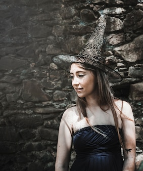 Young woman in dress and wizard hat looking aside
