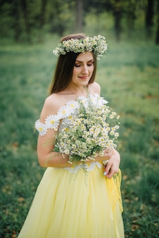 A young woman dressed in a beautiful tender dress and a wreath holds a bouquet of chamomiles in her hands