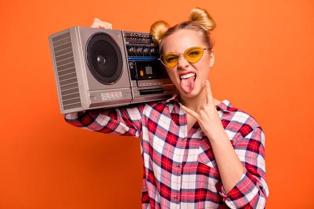 Молодая женщина, одетая в клетчатую рубашку, изолированную на оранжевом, с бумбоксом