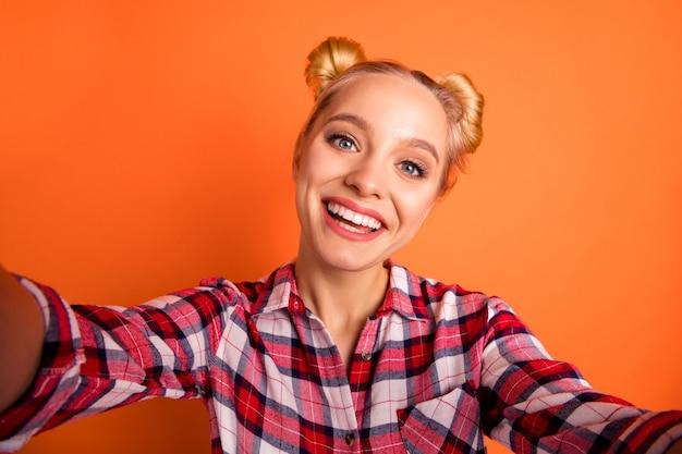 Молодая женщина, одетая в клетчатую рубашку, делает селфи на оранжевом фоне