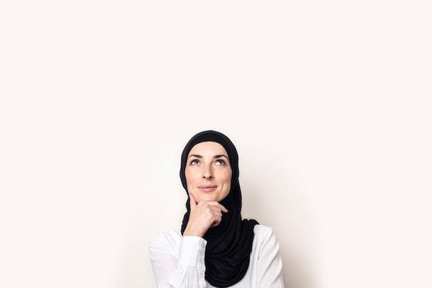 白いシャツとヒジャーブに身を包んだ若い女性は彼女のあごに手を握り、物思いにふける顔で見上げる