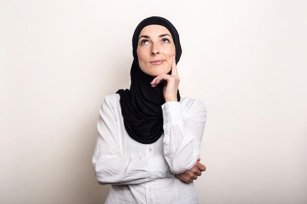 Молодая женщина, одетая в белую рубашку и хиджаб, подносит руку к подбородку и смотрит вверх с задумчивым лицом Premium Фотографии