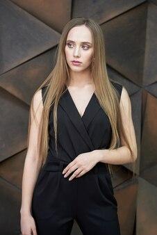 Молодая женщина одета в черный комбинезон, туфли на каблуках позирует. красивая белокурая девушка демонстрируя стильную умную одежду против стены