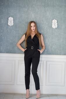 Молодая женщина одета в черный комбинезон, туфли на каблуках позирует.