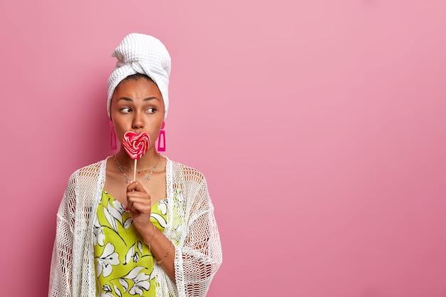 캐주얼 의류를 입은 젊은 여자, 심각하게 옆으로 보이는, 분홍색 벽, 빈 복사본 공간에 고립 된 달콤한 맛있는 심장 모양의 롤리팝으로 입을 다룹니다.