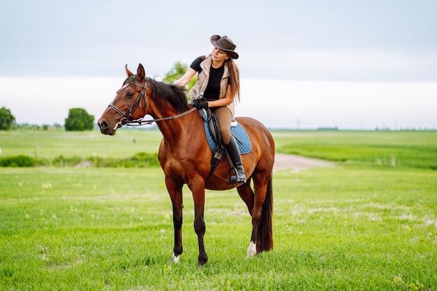녹색 필드에 갈색 말을 타고 옷과 모자를 타고 젊은 여자.