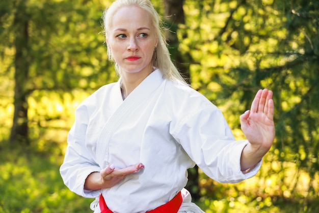 Young woman dressed in kimono practicing her karate moves in park - red belt