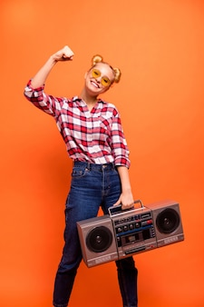 Young woman dressed in a plaid checked shirt isolated on orange with boombox