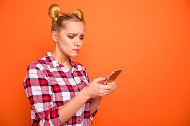 Young woman dressed in a plaid checked shirt isolated on orange with her phone