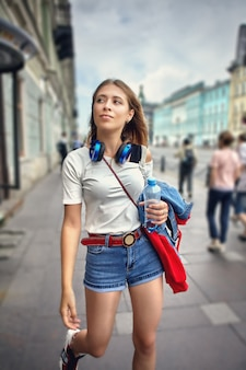 Young woman dressed in street style walks along the avenue.