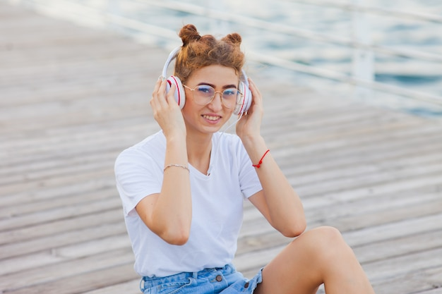 Young woman dressed in stylish clothes sits on the beach promenade and listen music in headphones