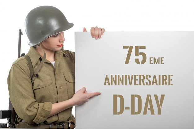 Young woman dressed in us  wwii military uniform with helmet showing signboard with d-day anniversary