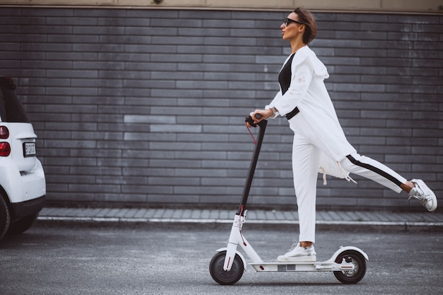 Young woman dressed in white riding scooter