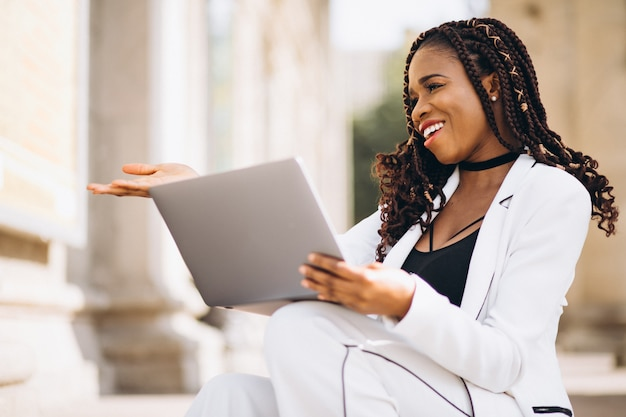 Young woman dressed in white using laptop