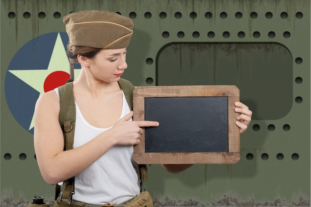 Young woman dressed in wwii military uniform with cap showing empty blank chalkboard with copy space
